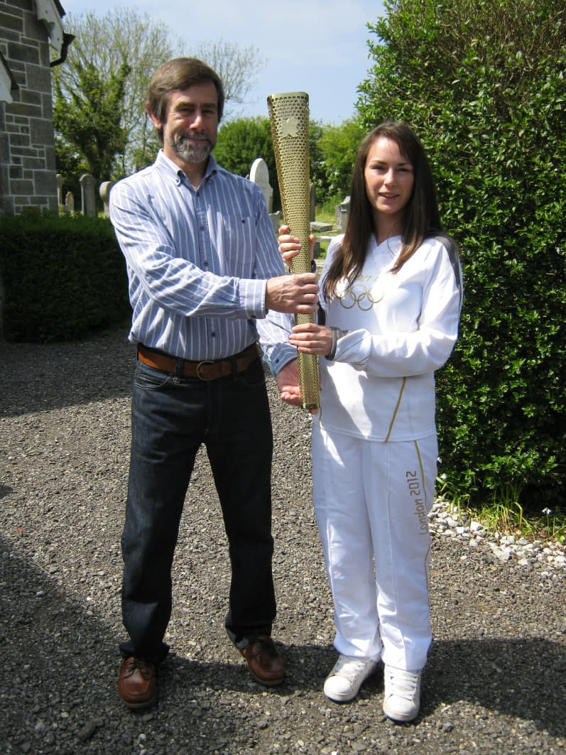 Samantha Woon presenting Roger Radcliffe with her Olympic torch